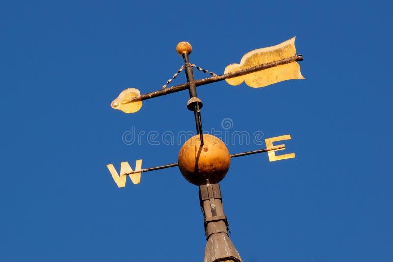 Ο χρυσός χρωμάτισε καιρικό vane που παρουσιάζει τη δύση και ανατολή με το βέλος ενάντια στο φωτεινό μπλε ουρανό στοκ φωτογραφία με δικαίωμα ελεύθερης χρήσης