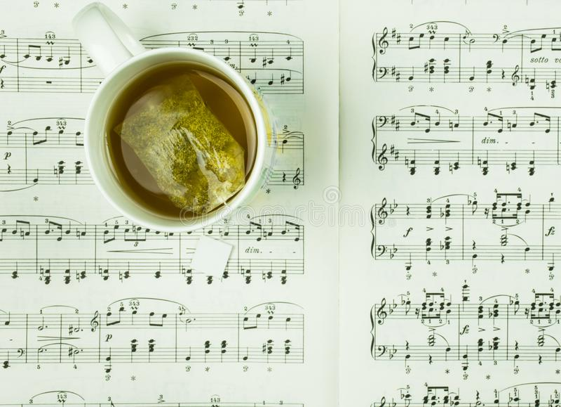 Ο χρόνος για τη μικρή διακοπή και το υπόλοιπο με το φλυτζάνι του τσαγιού και της μουσικής σημειώνει την έννοια στοκ εικόνα