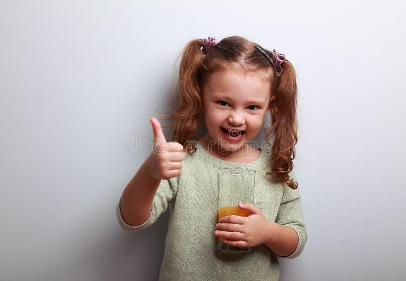 Ο χυμός κατανάλωσης κοριτσιών παιδιών γέλιου και παρουσίαση αντίχειρων υπογράφει επάνω στοκ φωτογραφία με δικαίωμα ελεύθερης χρήσης
