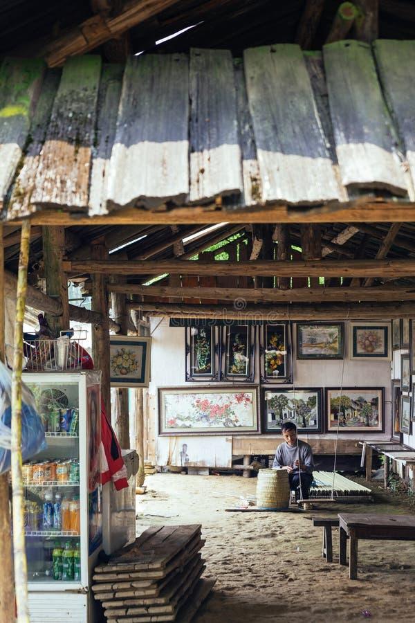 Ο χωρικός ατόμων κάθεται και υφαίνοντας καλάθι εσωτερικό με τα πλαίσια εικόνων στο υπόβαθρο στο χωριό γατών γατών σε Sa PA, Βιετν στοκ φωτογραφία