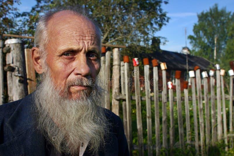 Ο χωρικός στέκεται πίσω από το φράκτη στύλων στον οποίο ξηροί κενοί κασσίτεροι στοκ φωτογραφία