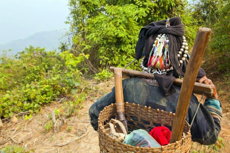 Ο χωρικός Akha φέρνει τα πράγματα σε την πίσω στο βουνό, Λάος στοκ φωτογραφία