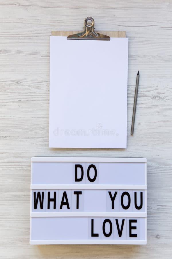 Ο χώρος εργασίας με την περιοχή αποκομμάτων, το φύλλο εγγράφου, το μολύβι και ο σύγχρονος πίνακας με το κείμενο ` κάνουν τι αγαπά στοκ φωτογραφία με δικαίωμα ελεύθερης χρήσης