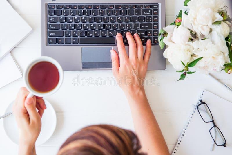 Ο χώρος εργασίας με το χέρι κοριτσιών ` s στο πληκτρολόγιο lap-top και το φλυτζάνι του τσαγιού, σημειωματάρια, γυαλιά, άσπρα peon στοκ εικόνες