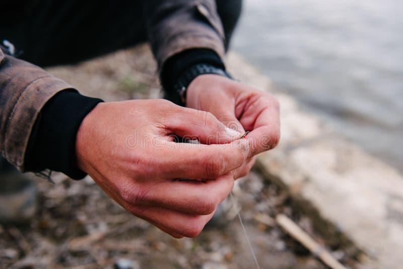 Ο ψαράς βάζει ένα σκουλήκι στο γάντζο στοκ φωτογραφία με δικαίωμα ελεύθερης χρήσης