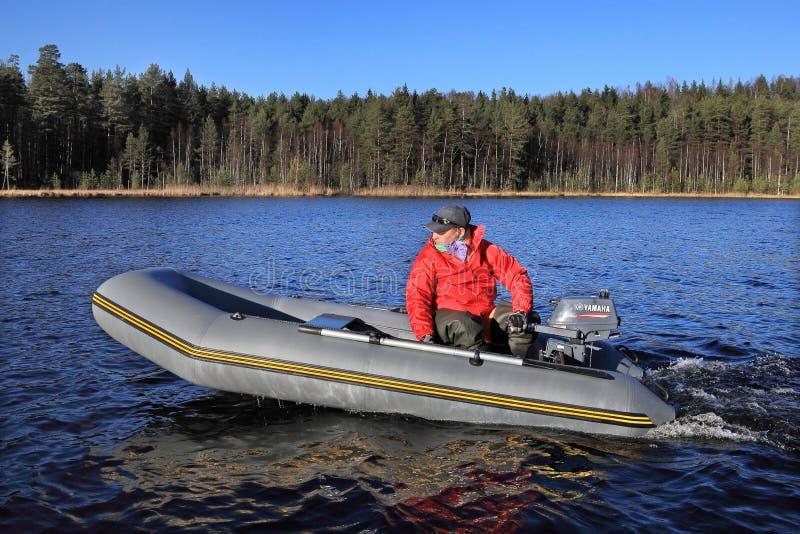 Ο ψαράς ελέγχει την γκρίζα διογκώσιμη λαστιχένια βάρκα με έναν εξωτερικό στοκ εικόνα