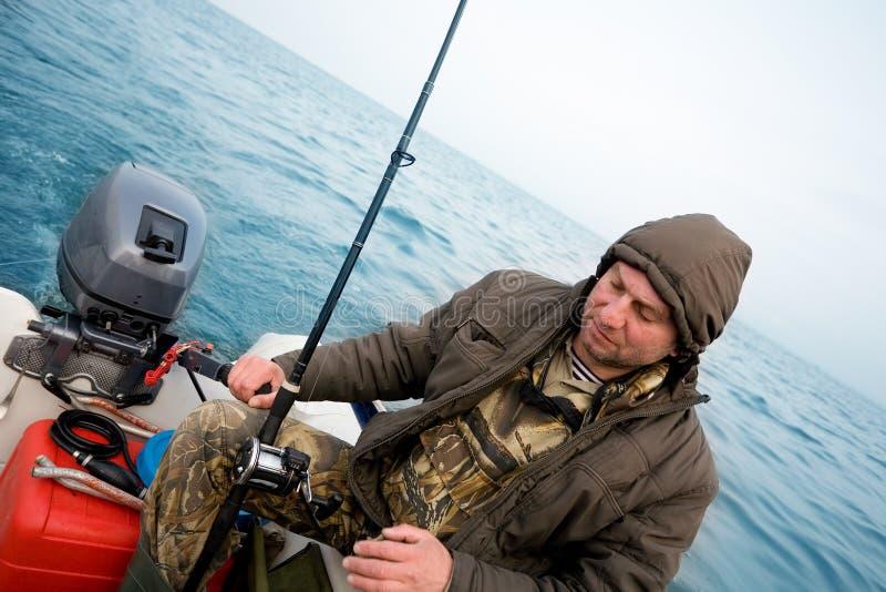 Ο ψαράς πιάνει έναν σολομό στη θάλασσα στοκ εικόνες