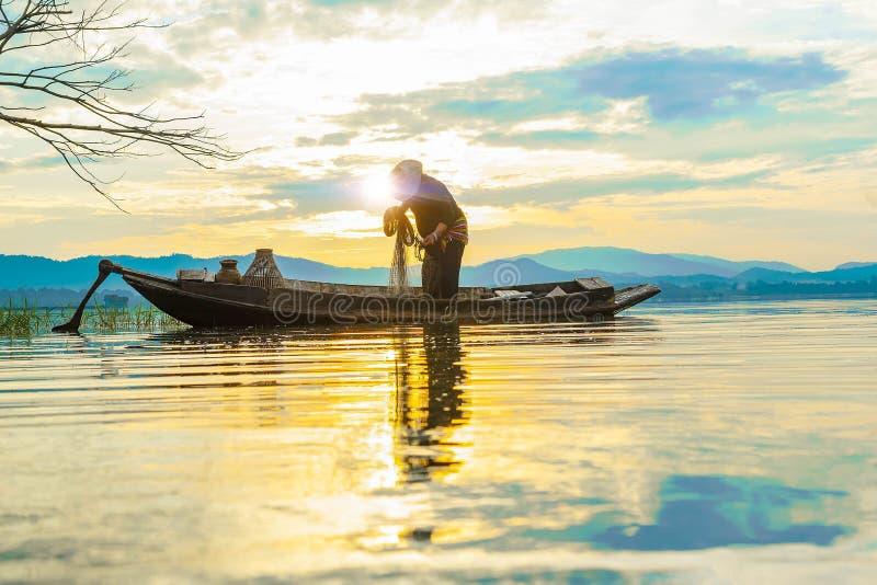 Ο ψαράς προετοιμάζει το δίχτυ ψαρέματος στην παλαιά βάρκα στα ξημερώματα λιμνών στοκ εικόνες με δικαίωμα ελεύθερης χρήσης