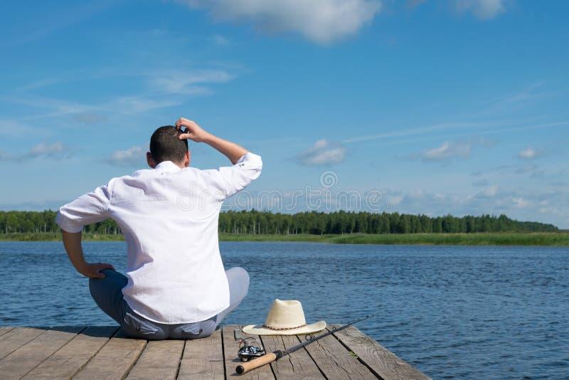 Ο ψαράς σκέφτεται πώς να πιάσει τα ψάρια σε έναν ποταμό στον ηλιόλουστο καιρό στοκ εικόνες