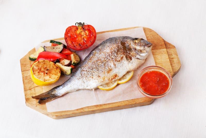 Ολόκληρα τα λαχανικά dorado άσπρων ψαριών, καλαμπόκι, πίνακας πιπεριών λεμονιών ντοματών απομόνωσαν seabass υποβάθρου στοκ φωτογραφίες