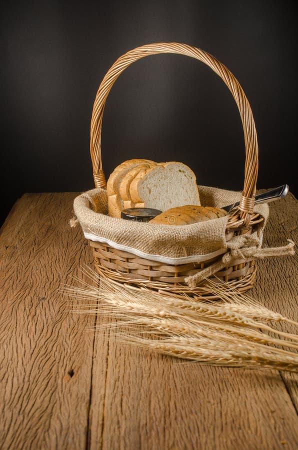 ολόκληρες ψωμί και μαρμελάδα σίτου στο καλάθι με το σιτάρι κριθαριού στοκ φωτογραφία με δικαίωμα ελεύθερης χρήσης
