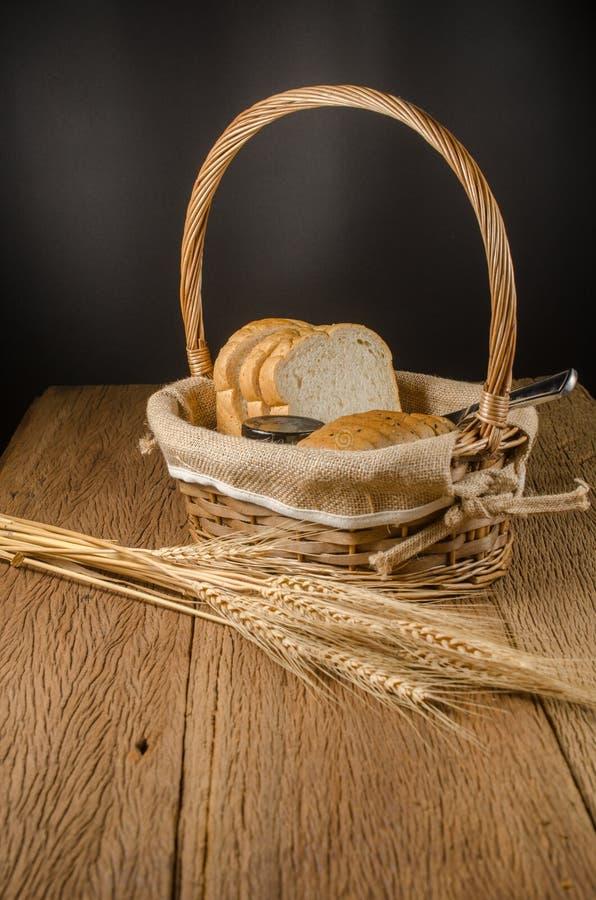 ολόκληρες ψωμί και μαρμελάδα σίτου στο καλάθι με το σιτάρι κριθαριού στοκ εικόνες