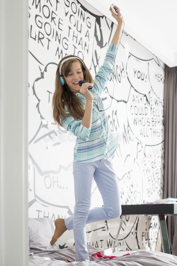 Ολόκληρος της μουσικής ακούσματος κοριτσιών τραγουδώντας στη βούρτσα γηα τα μαλλιά στο κρεβάτι στοκ φωτογραφία