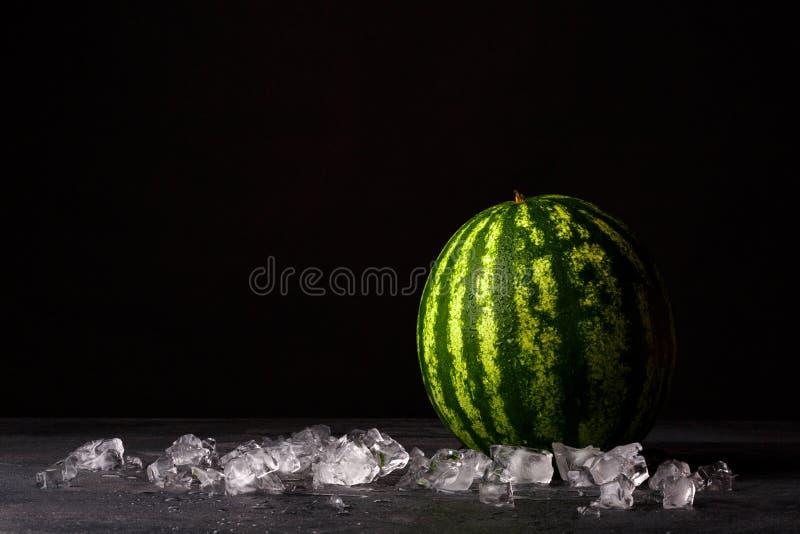 Ολόκληρο ένα μεγάλο καρπούζι σε ένα μαύρο επιτραπέζιο υπόβαθρο Πράσινο καρπούζι και συντριμμένος πάγος Κρύα και γλυκά θερινά πρόχ στοκ φωτογραφία με δικαίωμα ελεύθερης χρήσης