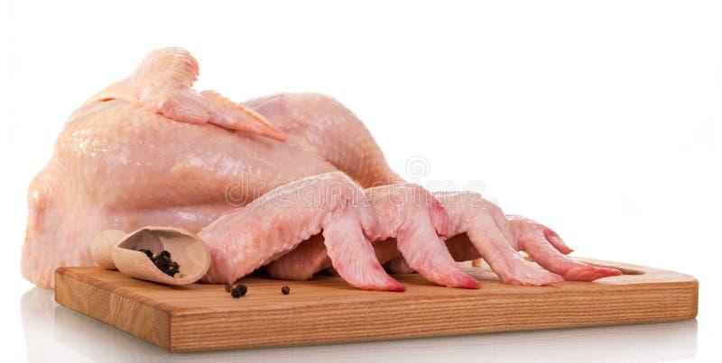 Ολόκληρο ακατέργαστο σφάγιο κοτόπουλου, φτερά, πίνακας, σέσουλα με τα πιπέρια που απομονώνεται στοκ φωτογραφία με δικαίωμα ελεύθερης χρήσης