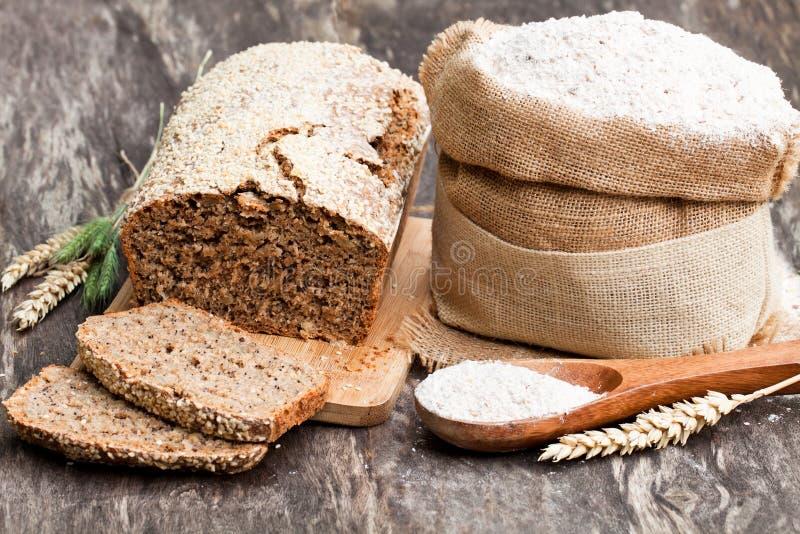 Ολόκληρο αλεύρι σιταριού και σπιτικό ψωμί με τους σπόρους στοκ εικόνες