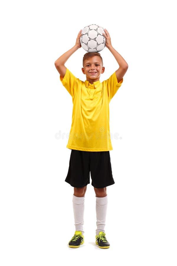Ολόκληρο πορτρέτο ενός νέου αθλητικού τύπου που κρατά μια σφαίρα επάνω από το κεφάλι του που απομονώνεται σε ένα άσπρο υπόβαθρο στοκ εικόνα
