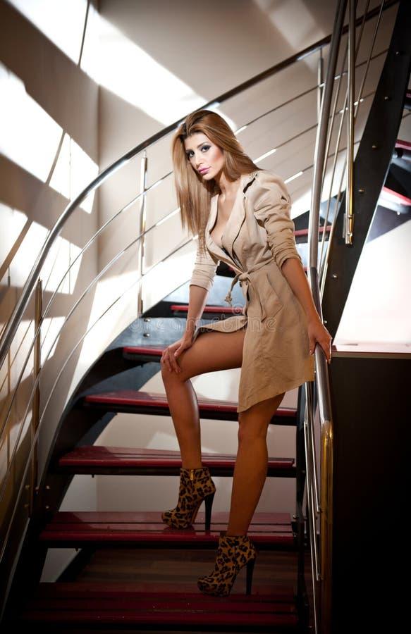 Ολόκληρο πορτρέτο της ξανθής γυναίκας που φορά μια τοποθέτηση παλτών provocatively στα βήματα σε ένα σύγχρονο εσωτερικό. Όμορφη γυ στοκ φωτογραφία με δικαίωμα ελεύθερης χρήσης