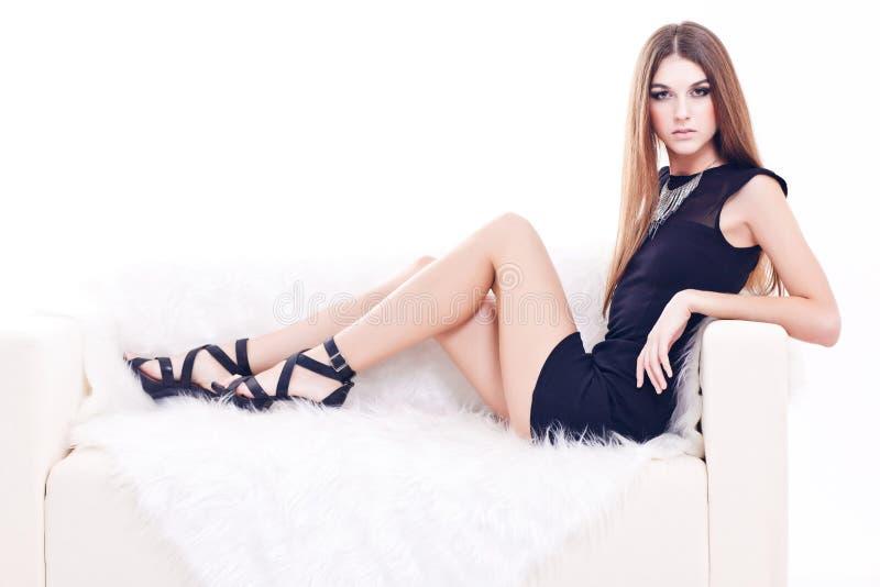 Ολόκληρο πορτρέτο της όμορφης νέας γυναίκας brunette στον καναπέ στοκ εικόνες