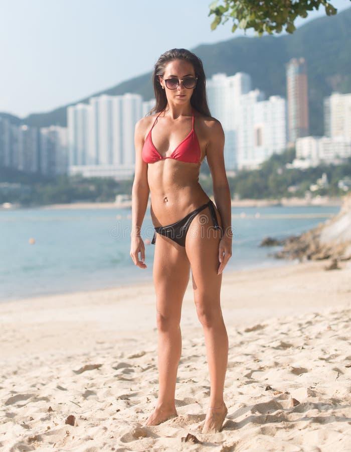 Ολόκληρο πορτρέτο του βέβαιου θηλυκού πρότυπου φορώντας μαγιό ικανότητας που στέκεται στην αμμώδη παραλία με τα υψηλά κτήρια μέσα στοκ εικόνα