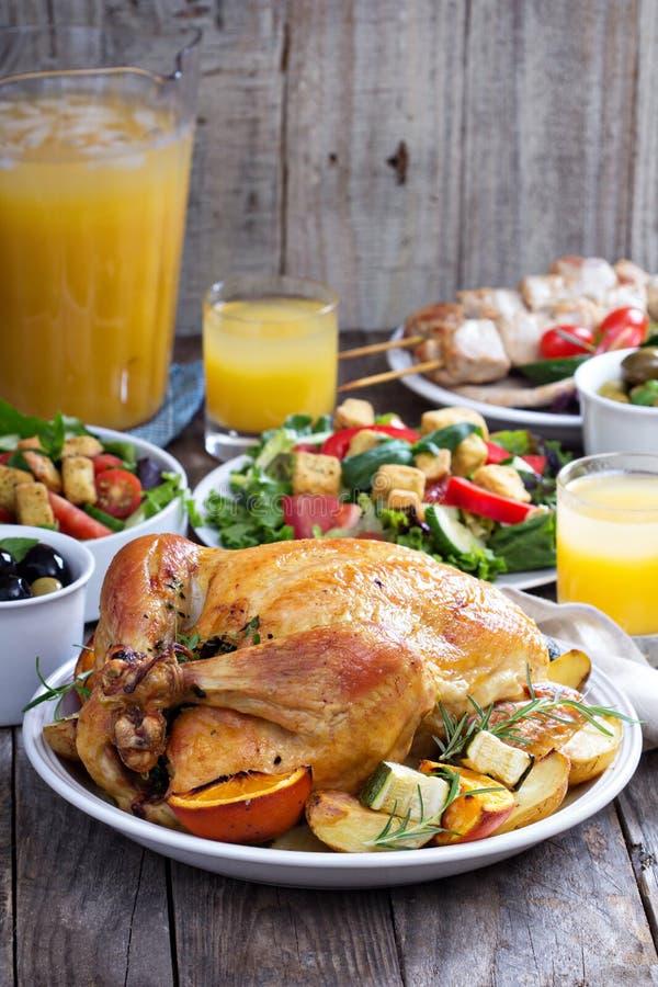Ολόκληρο ψημένο κοτόπουλο στον πίνακα γευμάτων στοκ εικόνες