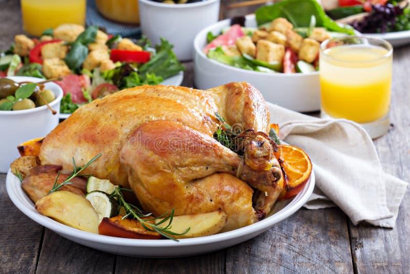 Ολόκληρο ψημένο κοτόπουλο στον πίνακα γευμάτων στοκ φωτογραφία με δικαίωμα ελεύθερης χρήσης