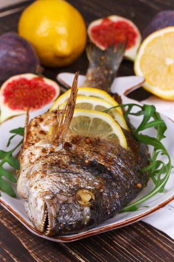 Ολόκληρο ψημένο στη σχάρα dorado ψαριών που εξυπηρετείται με το λεμόνι και τα σύκα στοκ εικόνα