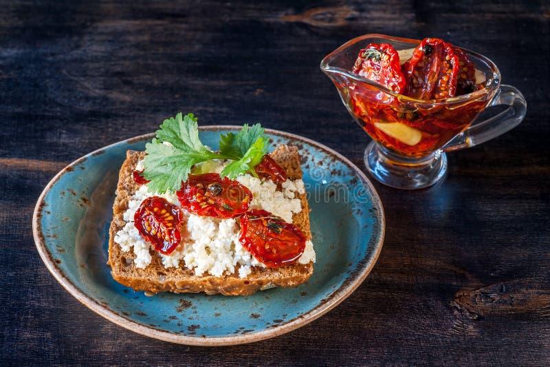 Ολόκληρο ψωμί σίτου με τις ξηραμένες από τον ήλιο ντομάτες, το τυρί εξοχικών σπιτιών και τα χορτάρια στοκ εικόνα