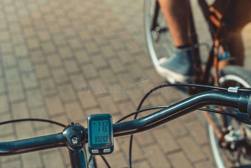 Οδόμετρο υπολογιστών ποδηλάτων στο τιμόνι στο υπόβαθρο ποδηλατών, πυροβολισμός άποψης στοκ φωτογραφίες