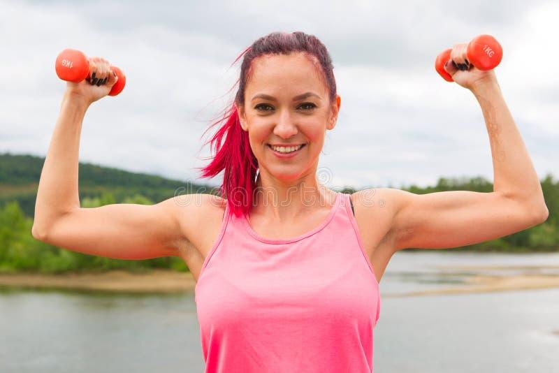 Ο όμορφος αθλητής κοριτσιών θέτει να ασκήσει με το μικρό αλτήρα βαρών υπαίθρια στοκ εικόνα