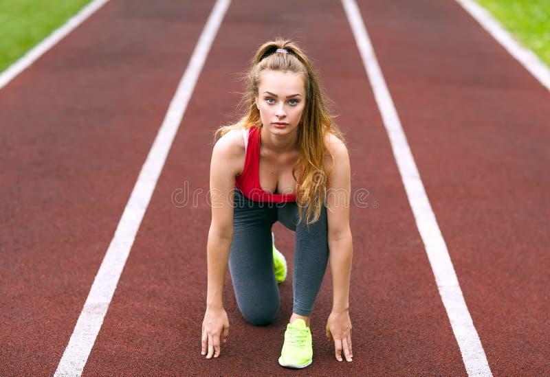Ο όμορφος αθλητής σε μια διαδρομή αγώνων είναι έτοιμος να τρέξει στοκ εικόνες