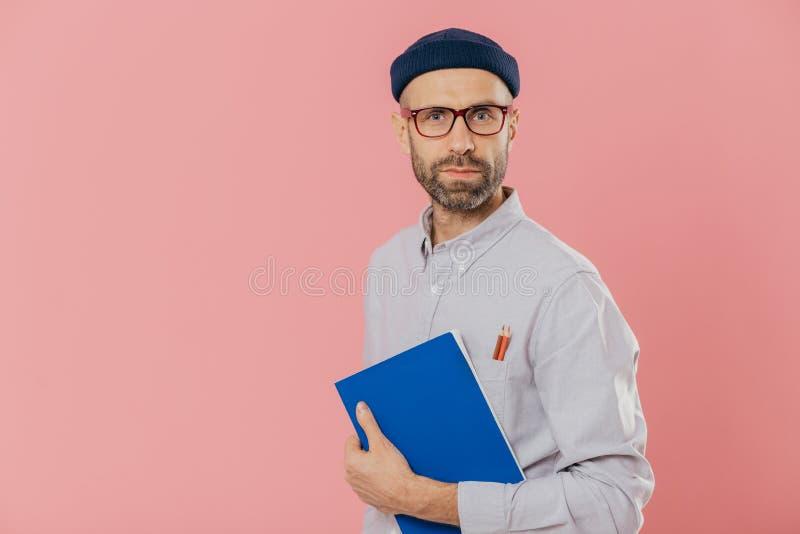 Ο όμορφος αρσενικός σχεδιαστής φορά τα μοντέρνα ενδύματα, έχει δύο μολύβια στην τσέπη του πουκάμισου, κρατά το μπλε σημειωματάριο στοκ εικόνες