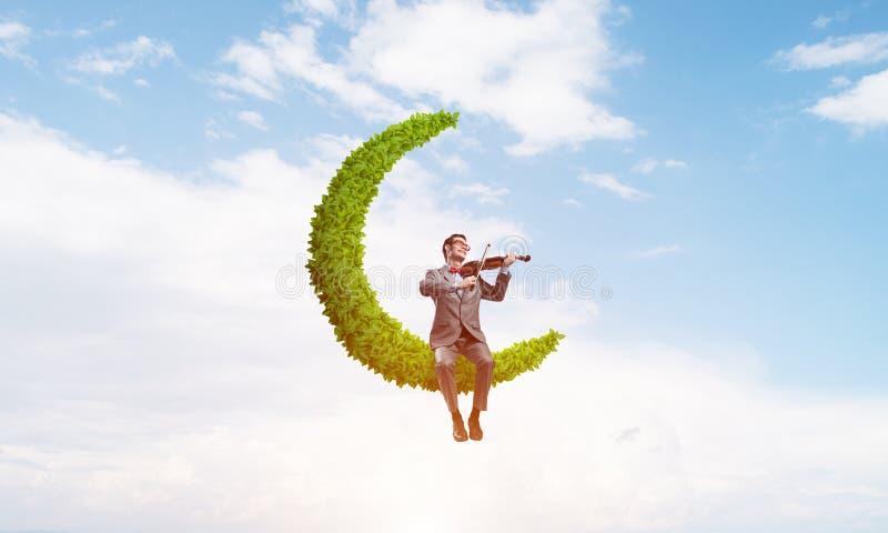 Ο όμορφος βιολιστής στο φεγγάρι στο μπλε ουρανό παίζει τη μελωδία του στοκ εικόνα με δικαίωμα ελεύθερης χρήσης