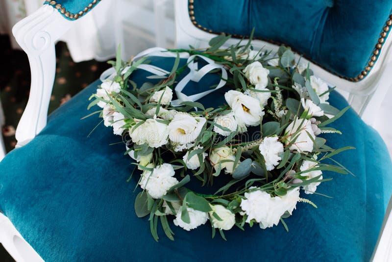 Ο όμορφος γαμήλιος κυκλίσκος βρίσκεται στην εκλεκτής ποιότητας μπλε μπεζ καρέκλα στοκ εικόνα με δικαίωμα ελεύθερης χρήσης