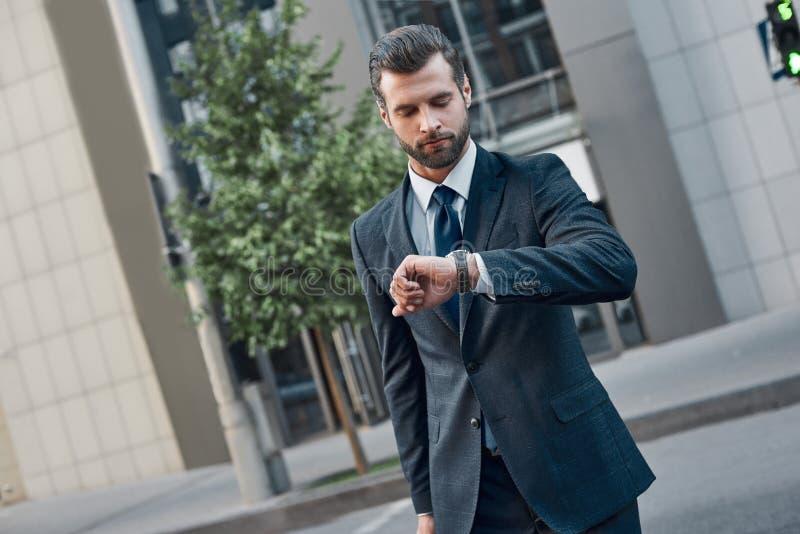 Ο όμορφος γενειοφόρος επιχειρηματίας στο κλασικό κοστούμι εξετάζει το ρολόι του στοκ εικόνα με δικαίωμα ελεύθερης χρήσης