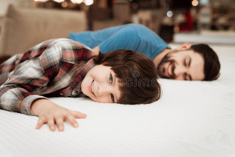 Ο όμορφος γενειοφόρος πατέρας με το νέο γιο εξετάζει το στρώμα για τη μαλακότητα στοκ φωτογραφίες