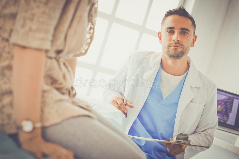 Ο όμορφος γιατρός μιλά με το νέο θηλυκό ασθενή και κάνει τις σημειώσεις καθμένος στο γραφείο του στοκ φωτογραφία