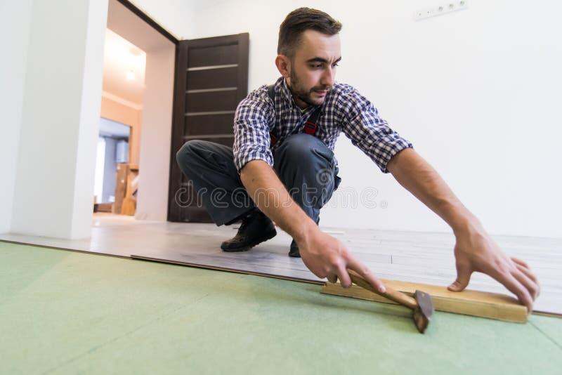 Ο όμορφος επισκευαστής που μετρά το ξύλινο δάπεδο με το σφυρί εγκαθιστά το φύλλο πλαστικού στοκ φωτογραφία με δικαίωμα ελεύθερης χρήσης