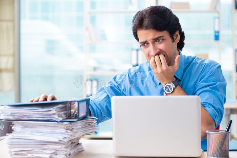 Ο όμορφος επιχειρηματίας δυστυχισμένος με την υπερβολική εργασία στο γραφείο στοκ φωτογραφία με δικαίωμα ελεύθερης χρήσης