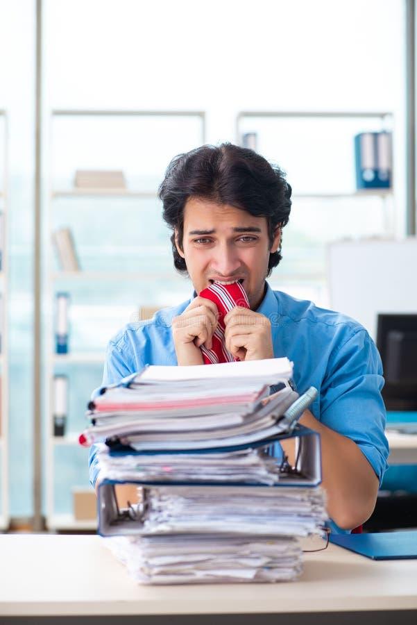 Ο όμορφος επιχειρηματίας δυστυχισμένος με την υπερβολική εργασία στο γραφείο στοκ εικόνες