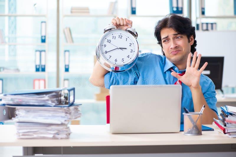 Ο όμορφος επιχειρηματίας δυστυχισμένος με την υπερβολική εργασία στο γραφείο στοκ εικόνα με δικαίωμα ελεύθερης χρήσης