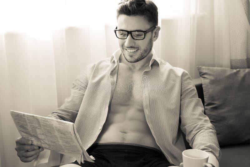 Ο όμορφος επιχειρηματίας, κάθεται από την εφημερίδα ανάγνωσης παραθύρων ξενοδοχείων και τον καφέ κατανάλωσης στοκ εικόνες