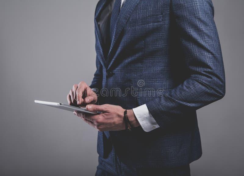 Ο όμορφος επιχειρηματίας μόδας έντυσε στο κομψό μπλε κοστούμι στο γκρίζο υπόβαθρο στοκ εικόνα