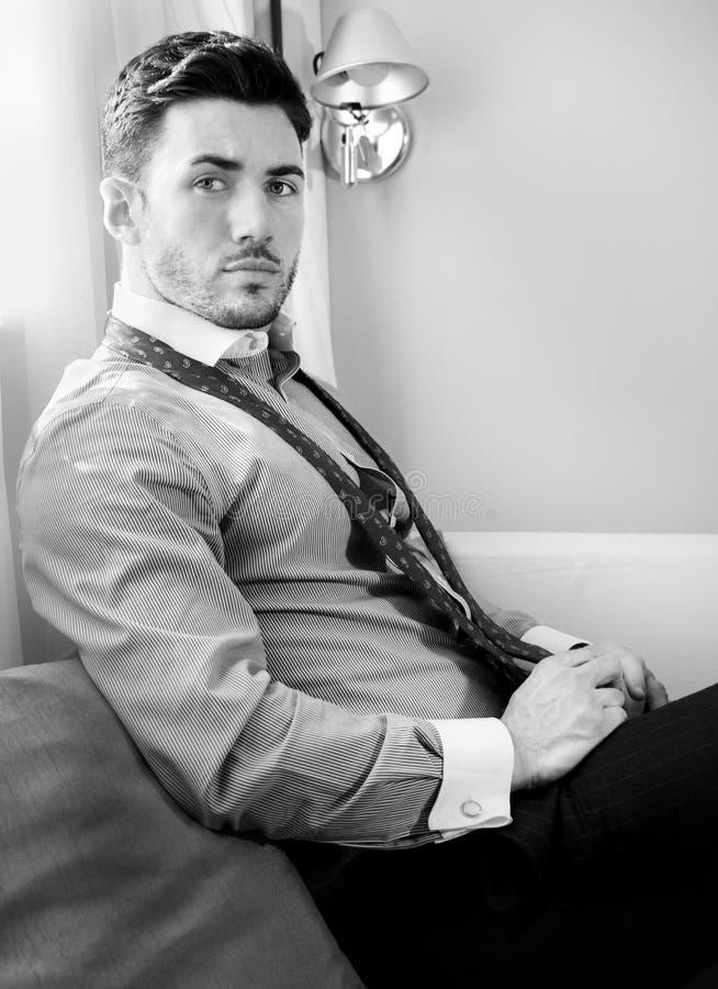 Ο όμορφος επιχειρηματίας που φορά το δεσμό και το ανοικτό πουκάμισο κάθεται μπροστά από το παράθυρο του δωματίου ξενοδοχείου στοκ εικόνα με δικαίωμα ελεύθερης χρήσης