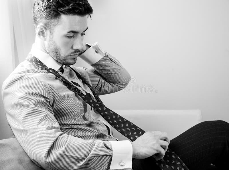 Ο όμορφος επιχειρηματίας που φορά το δεσμό και το ανοικτό πουκάμισο κάθεται μπροστά από το παράθυρο του δωματίου ξενοδοχείου στοκ φωτογραφία με δικαίωμα ελεύθερης χρήσης