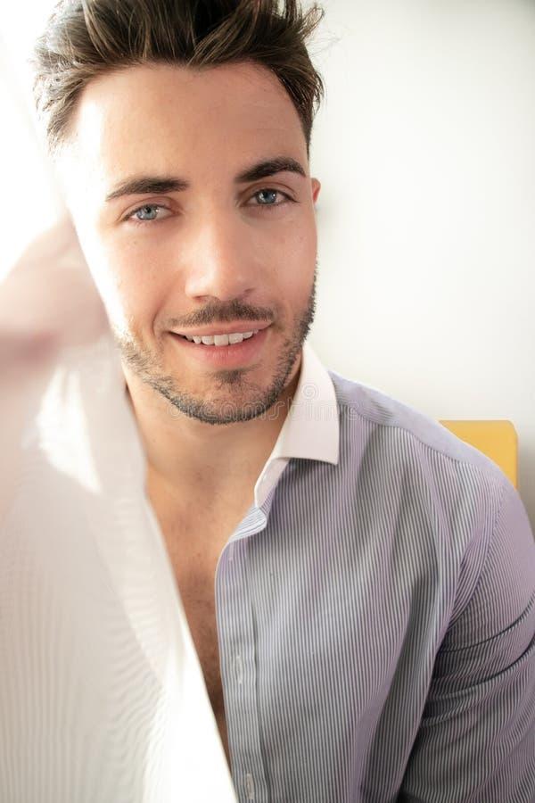 Ο όμορφος επιχειρηματίας που φορά το δεσμό και το ανοικτό πουκάμισο κάθεται μπροστά από το παράθυρο του δωματίου ξενοδοχείου στοκ εικόνες με δικαίωμα ελεύθερης χρήσης