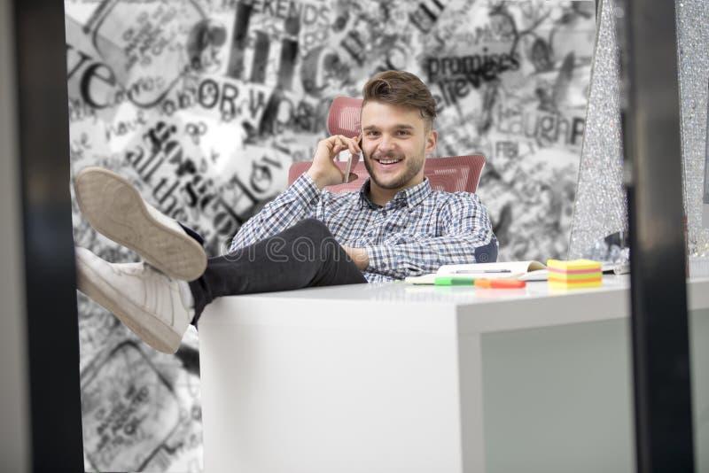 Ο όμορφος επιχειρηματίας στο κλασικό πουκάμισο χρησιμοποιεί ένα smartphone και χαμογελά καθμένος με τα πόδια στον πίνακα στην αρχ στοκ εικόνα με δικαίωμα ελεύθερης χρήσης