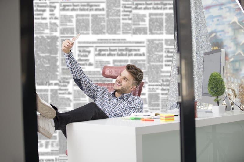 Ο όμορφος επιχειρηματίας στο κλασικό πουκάμισο χρησιμοποιεί ένα smartphone και χαμογελά καθμένος με τα πόδια στον πίνακα στην αρχ στοκ φωτογραφία με δικαίωμα ελεύθερης χρήσης