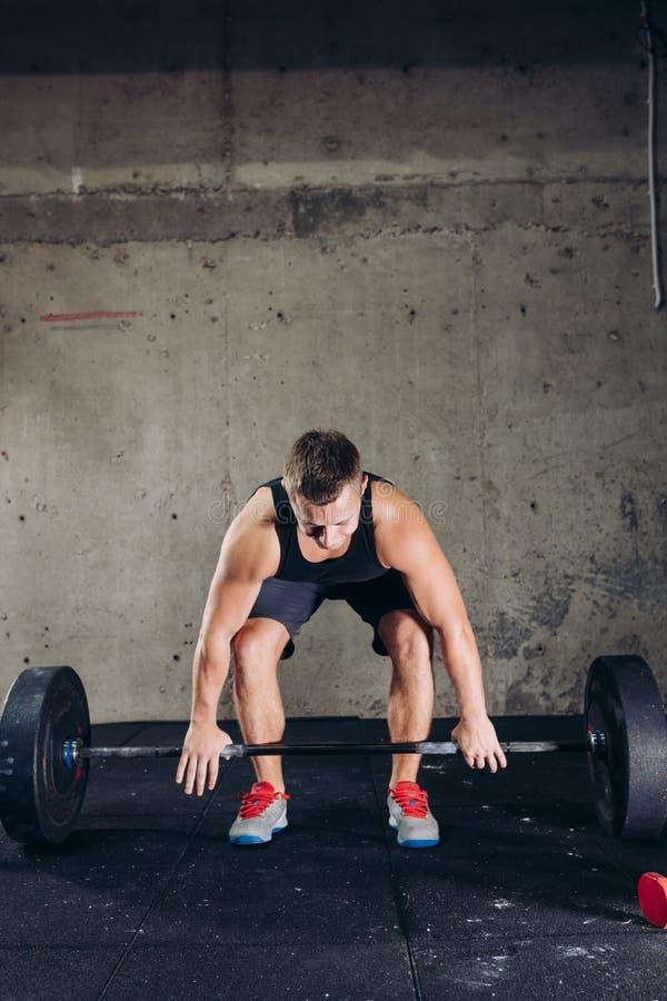 Ο όμορφος ισχυρός αθλητής πρόκειται να ανυψώσει ένα barbell στοκ εικόνα με δικαίωμα ελεύθερης χρήσης