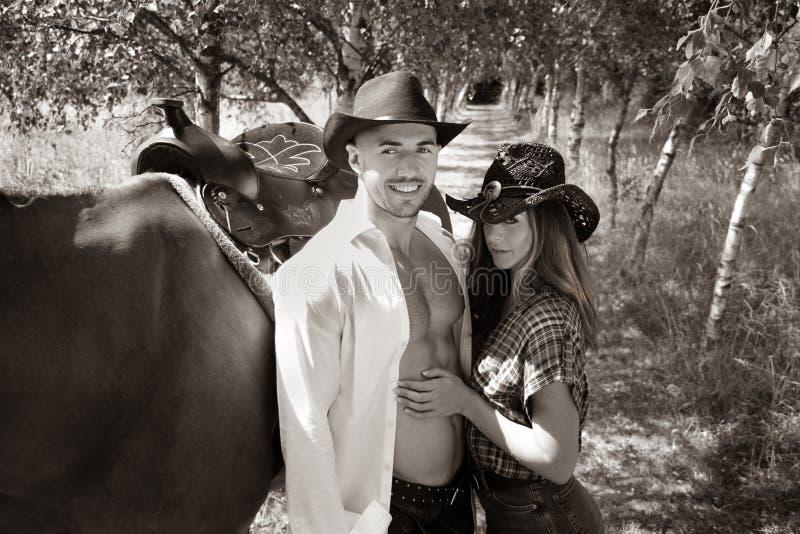 Ο όμορφος, όμορφος κάουμποϋ και cowgirl συνδέει με το άλογο και τη σέλα στην εκμετάλλευση και το φίλημα αγροκτημάτων στο αγρόκτημ στοκ φωτογραφίες
